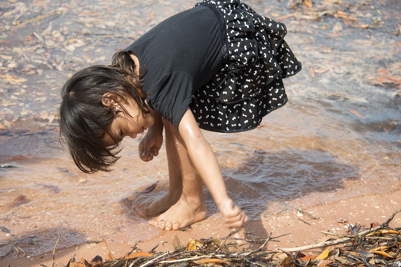 indigenous little girl looking for crabs Roebuck Bay Broome
